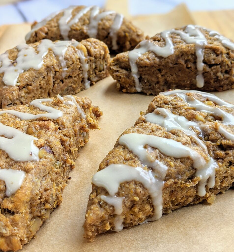 Pumpkin Walnut Scones on a sheet of parchment paper with icing drizzled on top