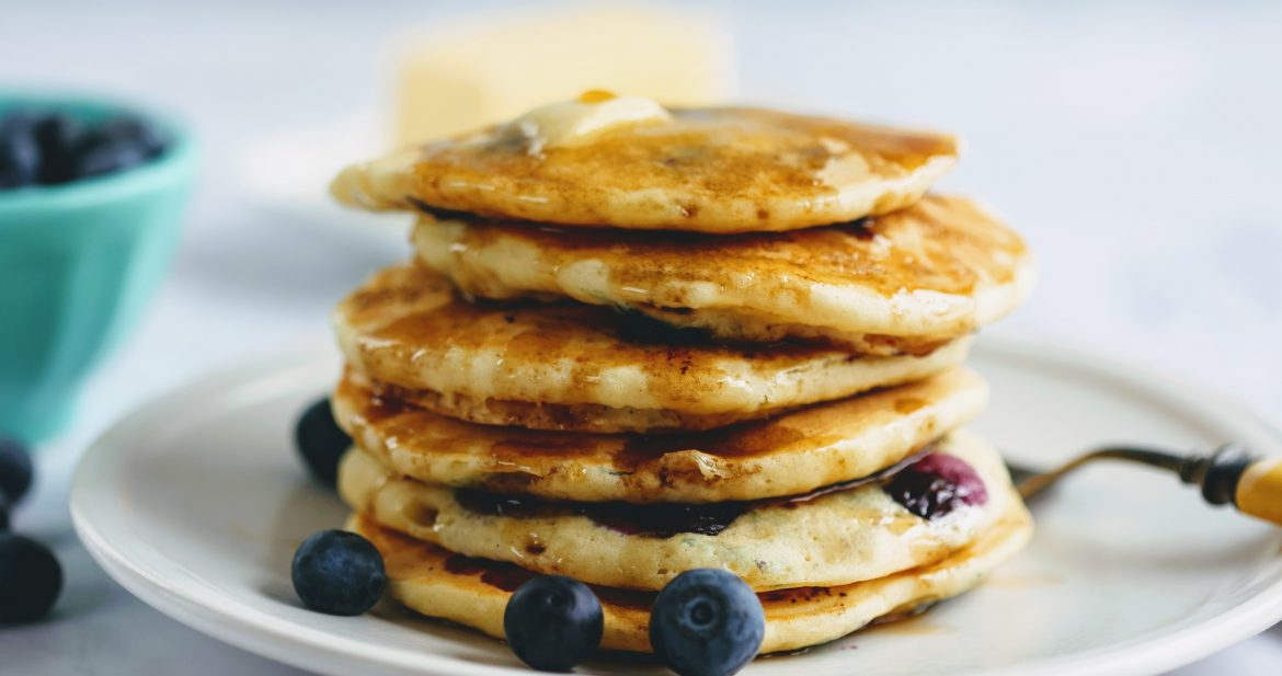 stack of blueberry buttermilk pancakes on plate with fork
