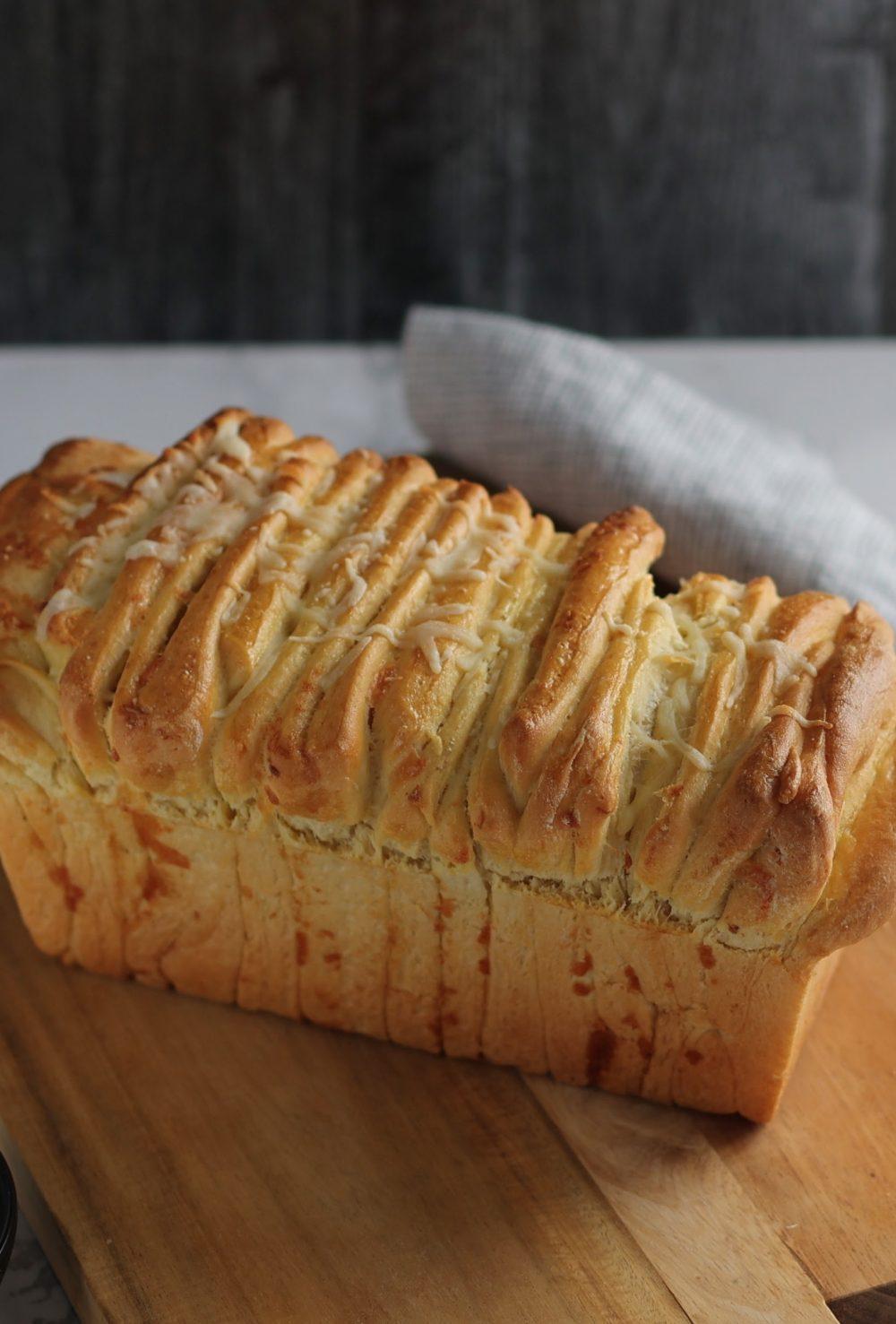 loaf of cheesy garlic pull-apart bread on a cutting board