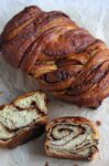 whole loaf cinnamon babka with 2 slices in front of it.