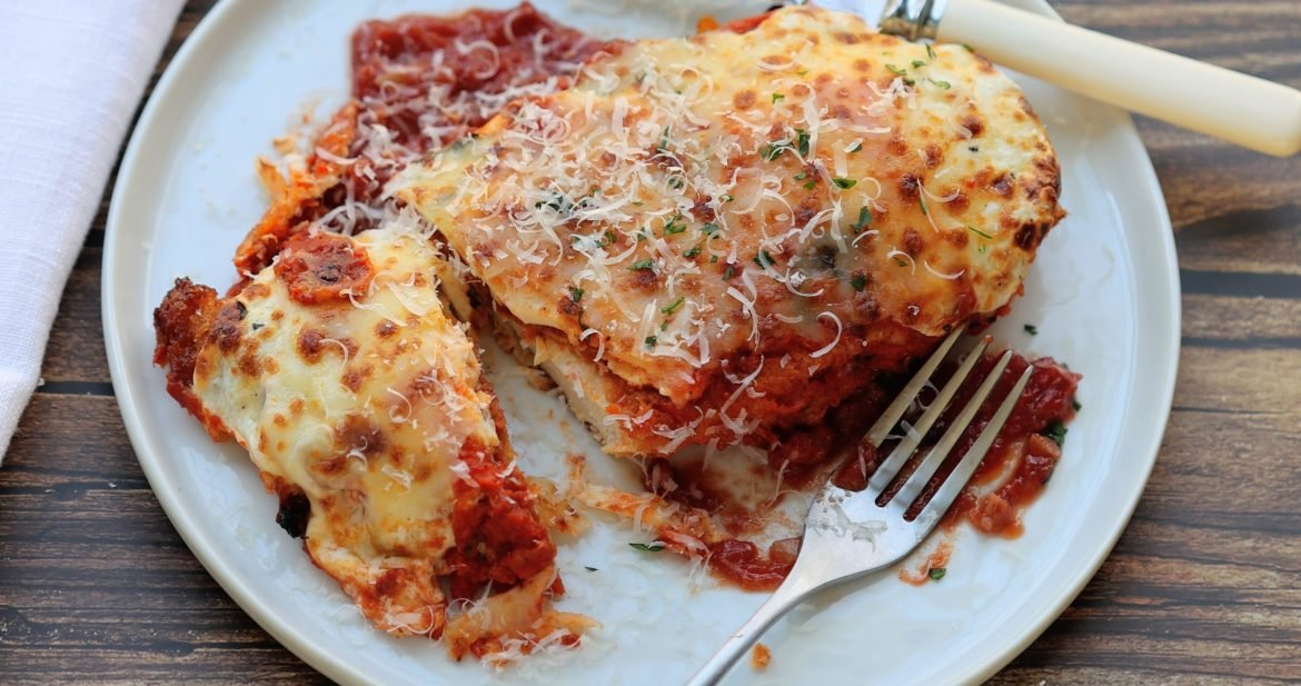 one piece of crispy chicken parmesan with fork and knife