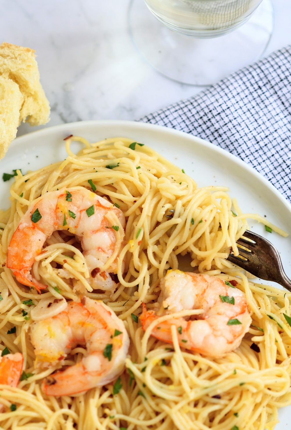 plate of shrimp scampi with angel hair pasta and glass of white wine
