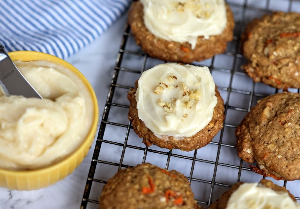 Carrot Cake Cookies on wore rack with bowl of cream cheese icing