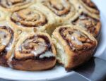 Cinnamon Buns out of pan and one being lifted out