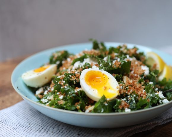 bowl of kale salad with toasted garlicky crumbs, crumbled feat, and 2 halves of a sift-boiled egg