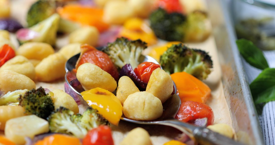 Easy Sheet Pan Gnocchi with Vegetables and Pesto with serving spoon on pan