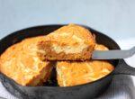 slice of pumpkin cream cheese cake on spatula above skillet